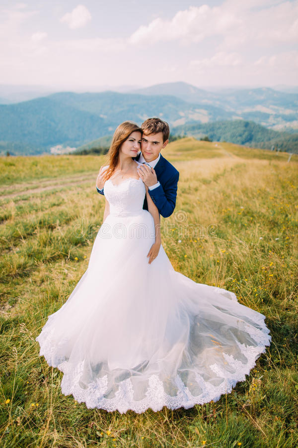 Unga romantiska brölloppar som poserar på soligt gräsfält med avlägsna Forest Hills och förträfflig himmel som bakgrund royaltyfria bilder