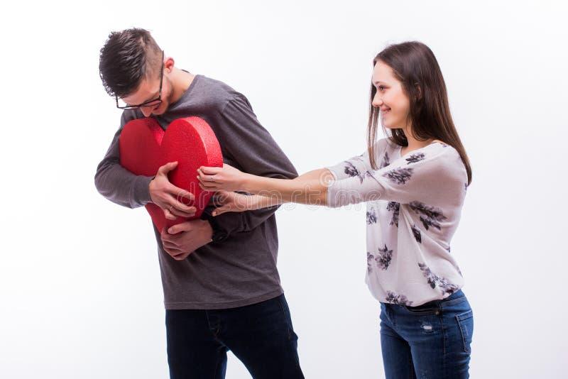 Unga romantiska förälskelsehipsterpar slåss för en röd hjärta, mansegrar royaltyfria bilder