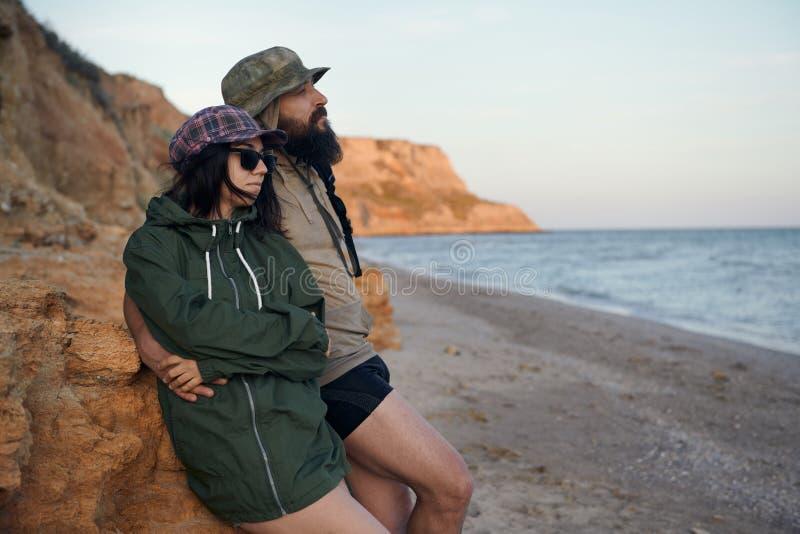 Unga romantiska handelsresande som ser till strandhimlen som tycker om solnedgången på havet - förälskelse, sommar och loppbegrep arkivbild
