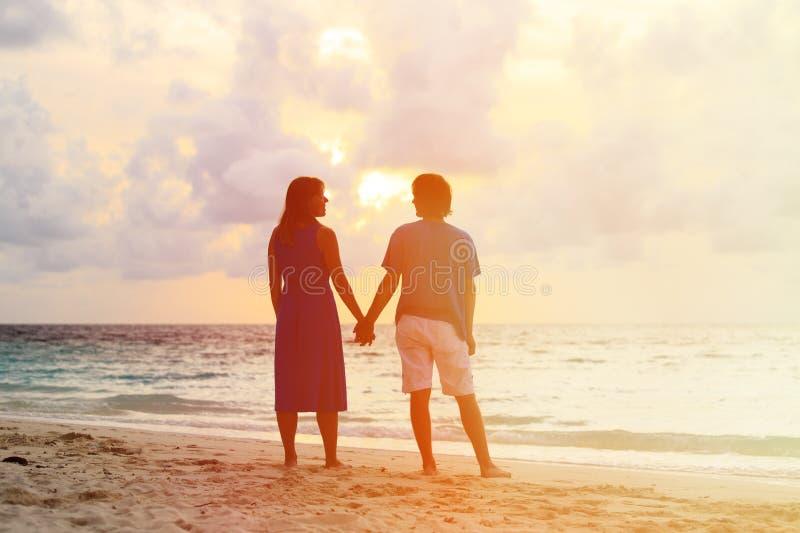 Unga romantiska par på stranden på solnedgången fotografering för bildbyråer