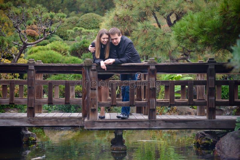 Unga romantiska par som kramar yttersidan på bron royaltyfria bilder