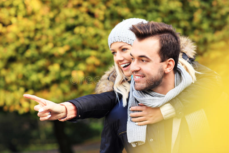 Unga romantiska par som pekar i parkera i höst arkivfoton