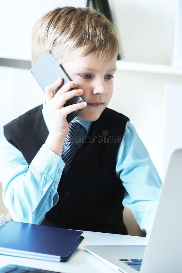 Unga s?kra ut?vande samtal f?r aff?rsmanframstickandepojke i regeringsst?llning p? telefonen som sitter p? skrivbordet med b?rbar arkivbilder