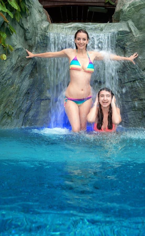 Unga sexiga kvinnor som tycker om det fallande vattnet av vattenfallet arkivfoton
