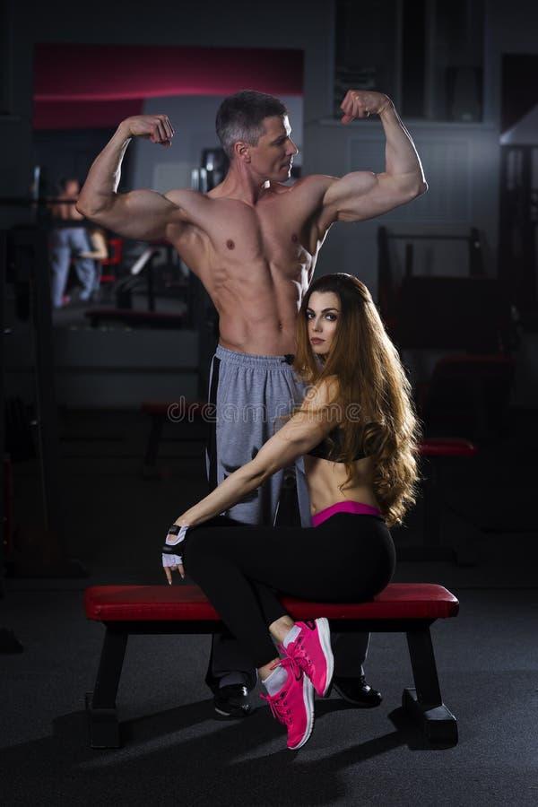 Unga sexiga par, idrotts- man och kvinna efter konditionövning, perfekt muskulös kropp royaltyfria bilder