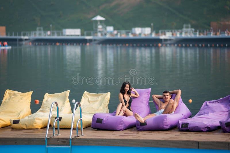 Unga sexiga par på dämpade dagdrivare av simbassängen och sjö på bakgrunden arkivbild