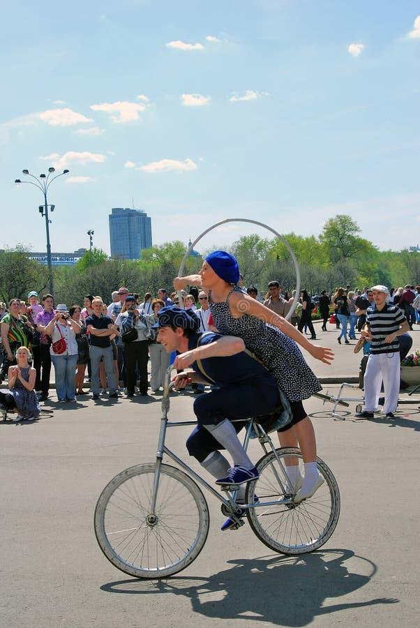 Unga skådespelare som utför i Gorkyen, parkerar Wwoman och mannen rider en cykel arkivbilder