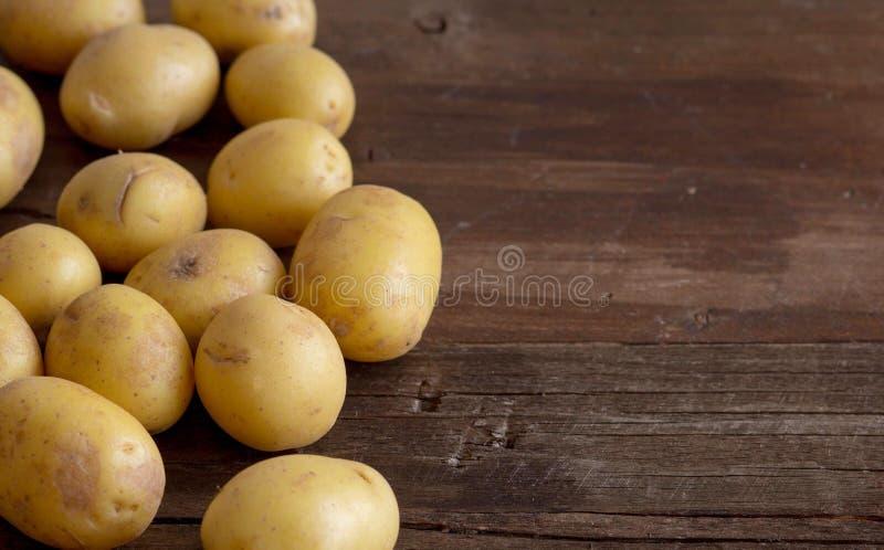 Unga små potatos på träbakgrund royaltyfria foton