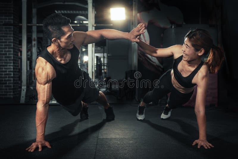 Unga sportiga par som tillsammans utarbetar på idrottshallen, konditionmannen och kvinnan som in ger sig höga fem efter utbildnin royaltyfri fotografi