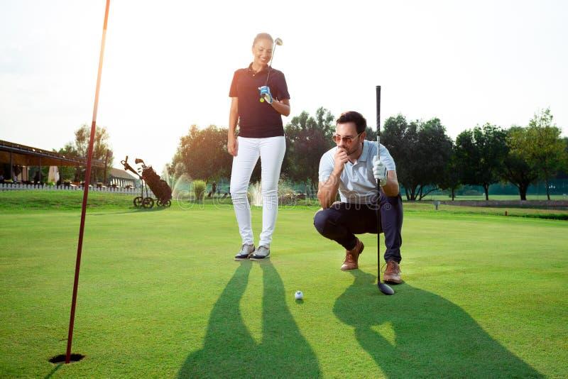 Unga sportive par som spelar golf på en golfbana royaltyfri fotografi