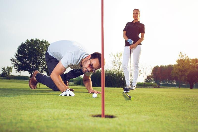 Unga sportive par som spelar golf p? en golfbana royaltyfria bilder