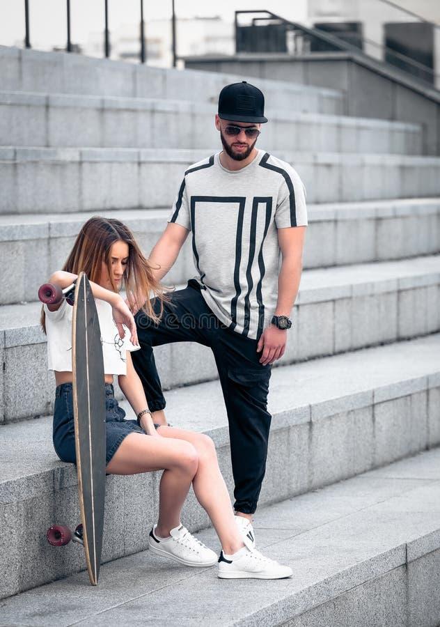 Unga stilfulla hipsters kopplar ihop på de konkreta nivåerna royaltyfria bilder