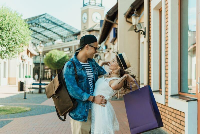 Unga stilfulla par med shoppingpåsar som kramar på gatan arkivbilder
