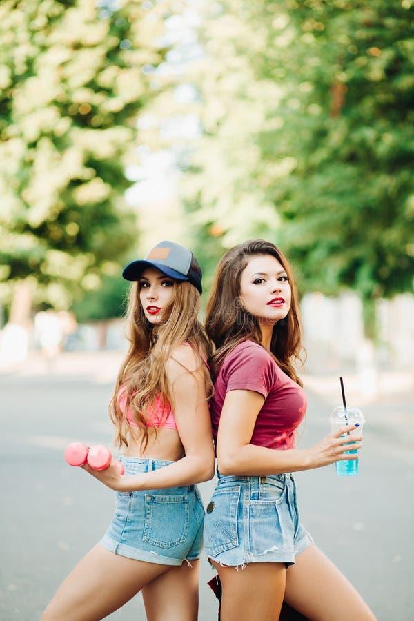 Unga stilfulla systrar som står tillbaka göra tillbaka övning på, parkerar arkivfoto