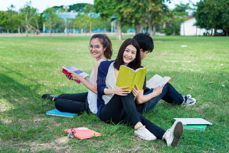Unga studenter grupperar att le med mappar bokar royaltyfri foto