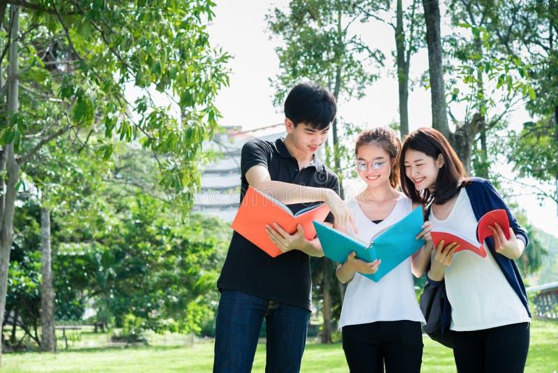 Unga studenter grupperar att se skolamappar i utbildningsuniversitetsområdeuniversitet arkivfoton