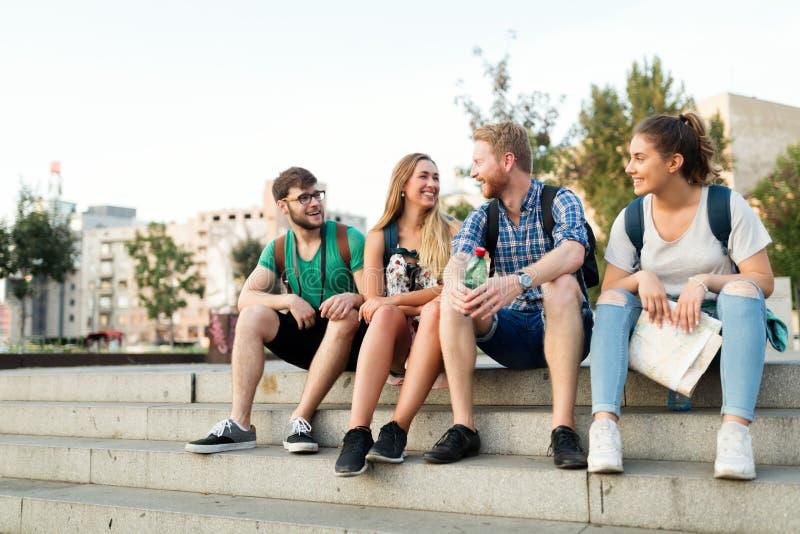 Unga studenter som är lyckliga på universitetsområdetrappa royaltyfri foto