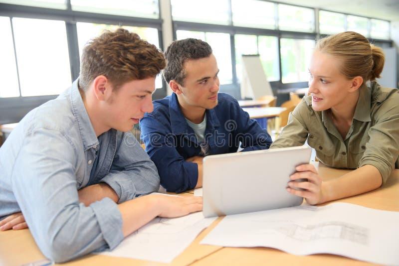 Unga studenter som arbetar på den digitala minnestavlan på skolan royaltyfria bilder