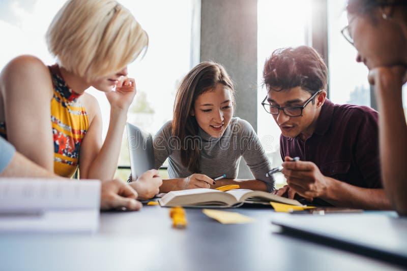 Unga studenter som arbetar på skolauppgift i arkiv arkivbilder