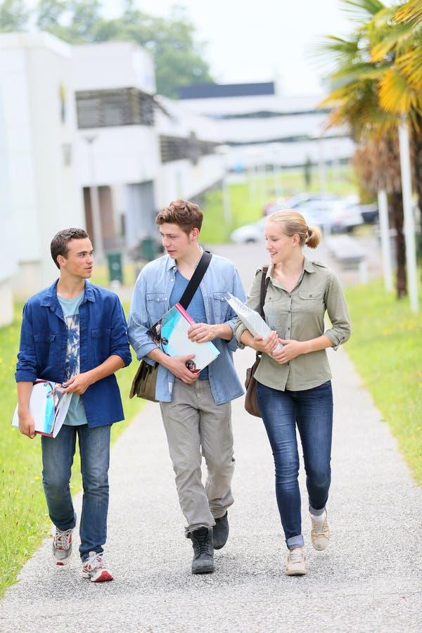 Unga studenter som går utanför universitetsområde arkivbilder