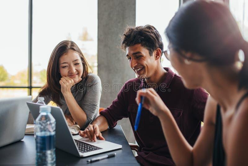 Unga studenter som studerar tillsammans genom att använda bärbara datorn fotografering för bildbyråer