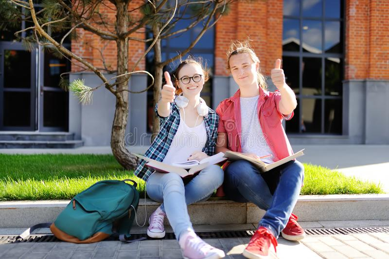 Unga studenter visar sikttummar upp och bra lycka royaltyfria bilder