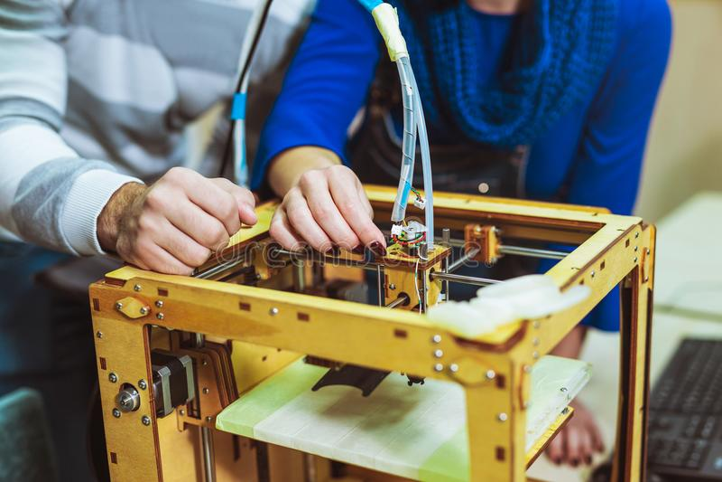 Unga studentforskare som använder en innovativ skrivare 3D royaltyfri bild
