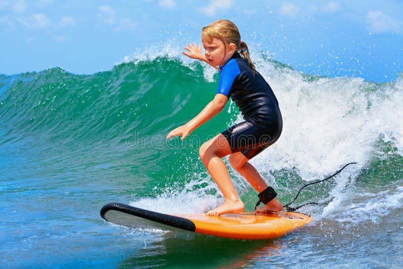 Unga surfareritter på surfingbrädan med gyckel på havet vinkar arkivbilder