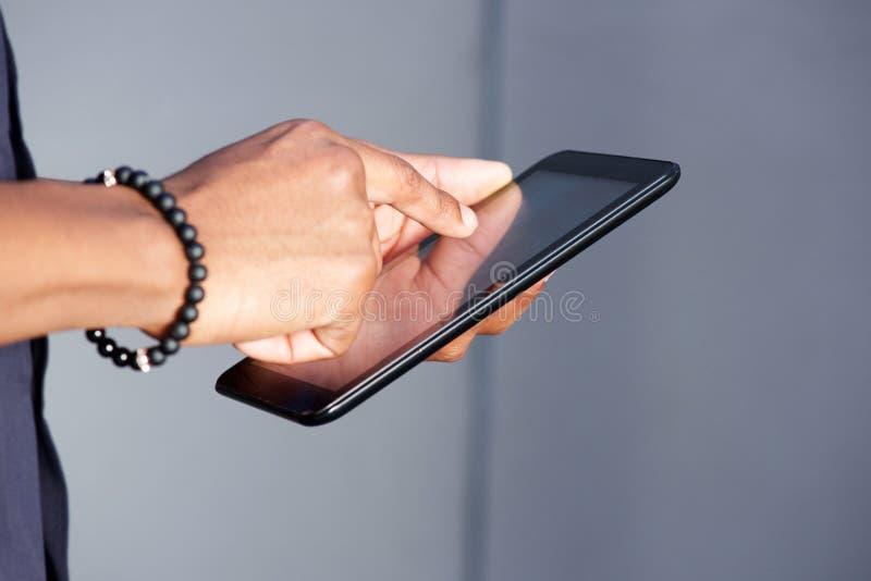 Unga svart manhänder genom att använda den digitala minnestavlan fotografering för bildbyråer