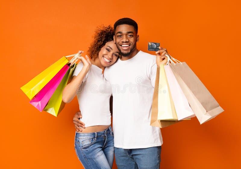 Unga svarta par med den shoppingpåsar och kreditkorten royaltyfri bild