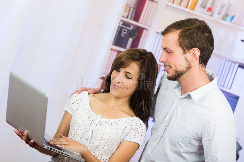 Unga tillfälliga attraktiva par genom att använda bärbara datorn fotografering för bildbyråer