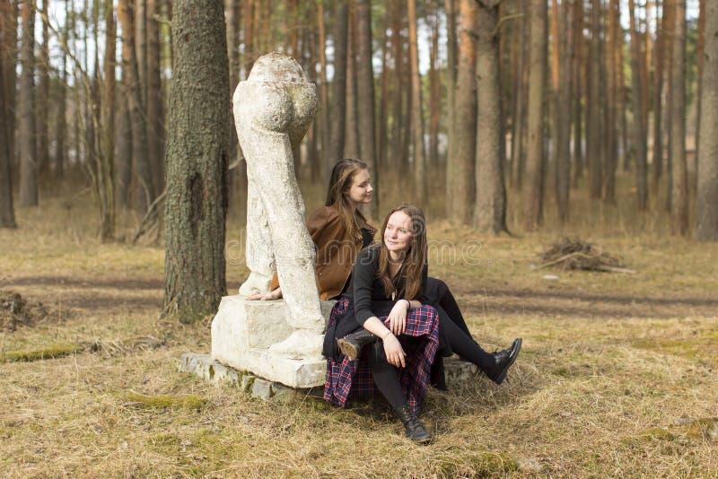 Unga tonåriga flickor som sitter på de gamla skulpturerna i parkera Natur arkivfoton