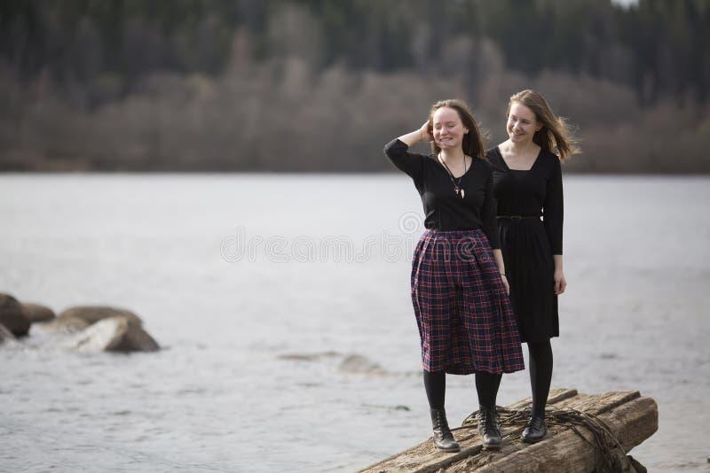 Unga tonåriga flickor som sitter på de gamla skulpturerna i parkera Natur royaltyfri fotografi