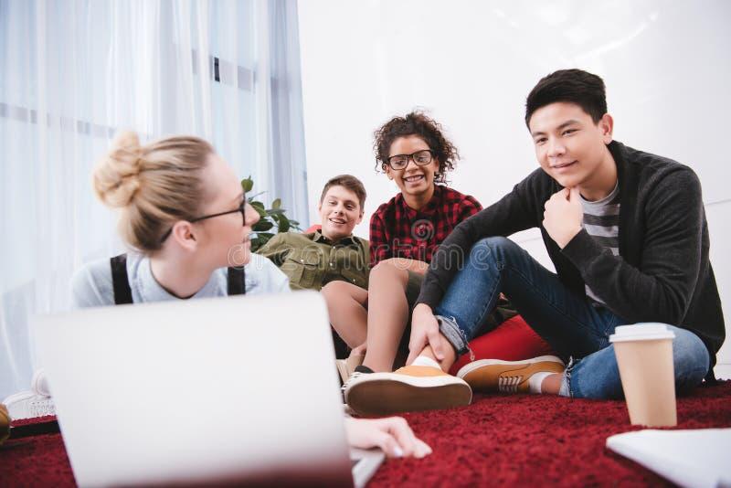 unga tonåriga studenter som ligger på matta med anteckningsböcker och att se fotografering för bildbyråer