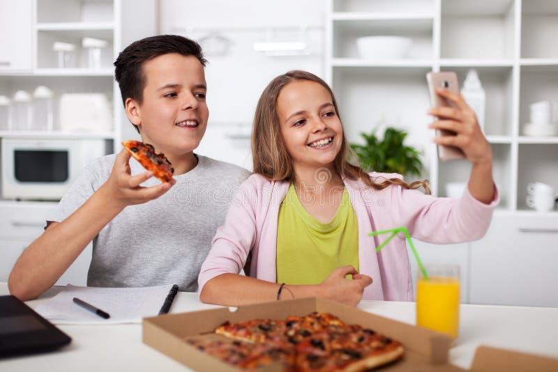 Unga tonåringar som tar en selfie med de och pizza som de delar i köket arkivbild