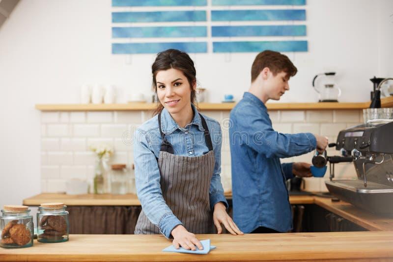 Unga trevliga baristas i enhetligt arbete på stången kontrar royaltyfri fotografi