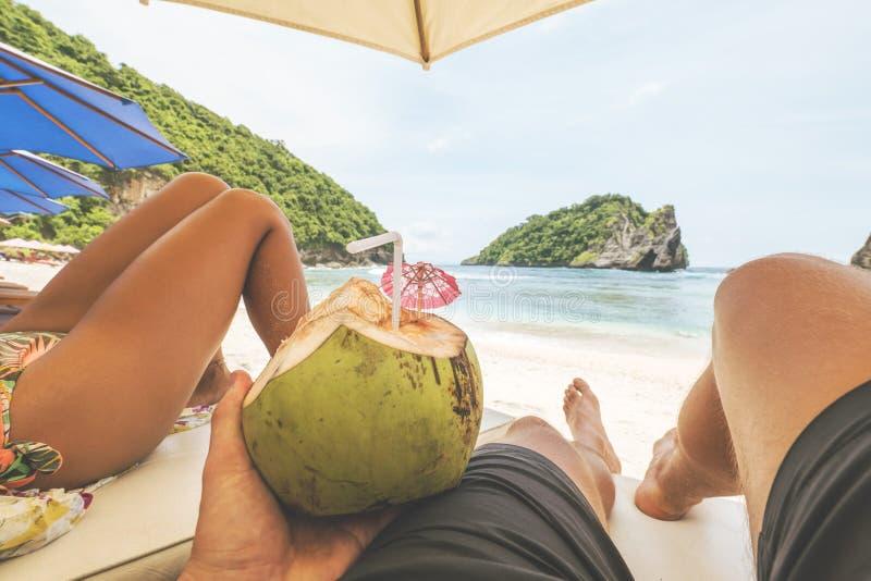 Unga turist- par som kopplar av på Sandy Beach på den tropiska paradisön GoPro första personsikt POV Nusa Penida arkivbild