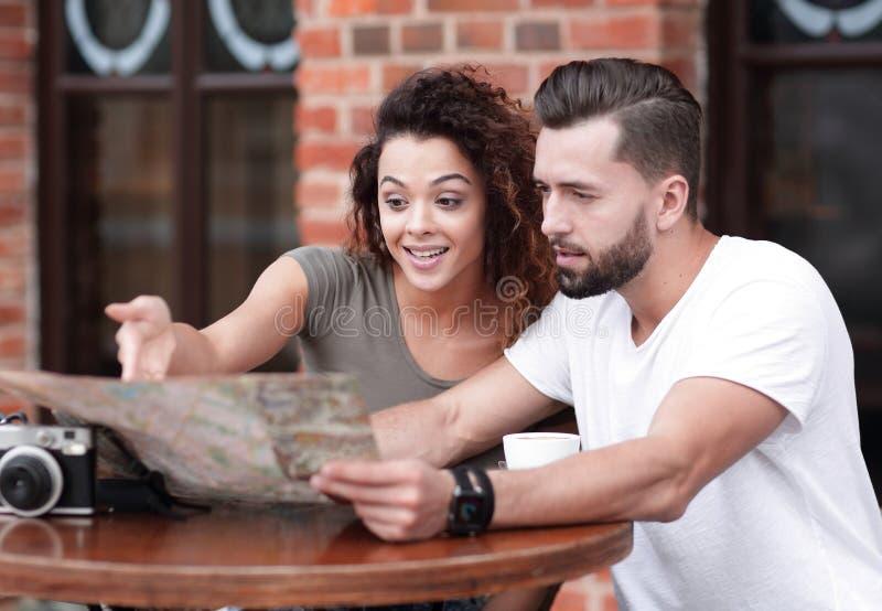 Unga turister som har kaffe på kafé- och läsningöversikten royaltyfri foto