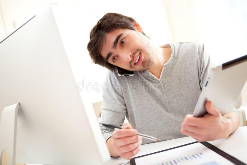 Unga upptagna män på kontoret genom att använda minnestavlan och smartphonen arkivfoto
