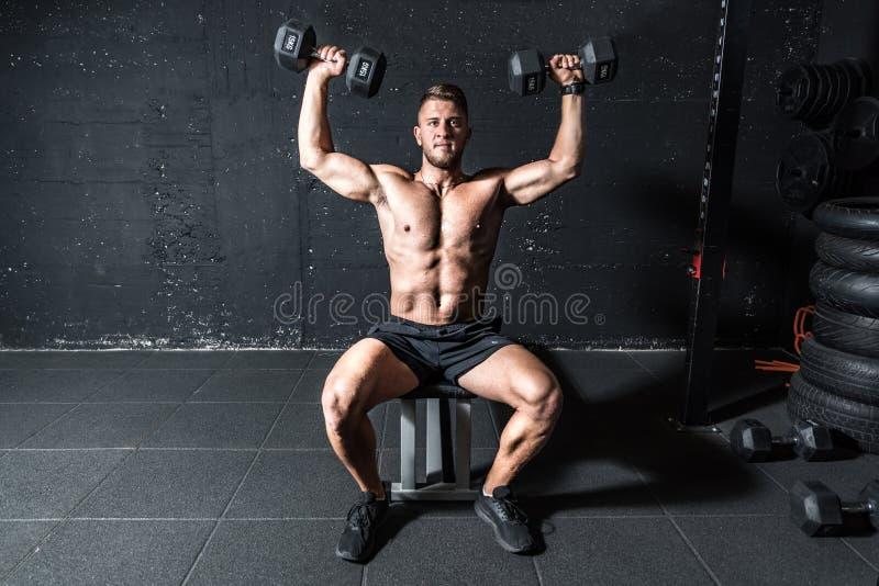 Unga, välvilliga män tar hand om träning med två dumbom i den gym mörka bilden med skuggor som riktiga människor royaltyfri fotografi