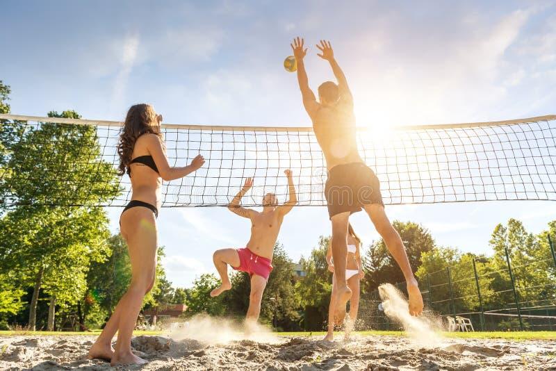 Unga vänner för grupp som spelar volleyboll på stranden royaltyfria foton