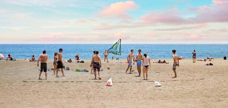 Unga vänner för grupp som spelar volleyboll på stranden arkivfoto