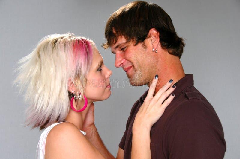 Unga vänner omkring som ska kyssas royaltyfria foton
