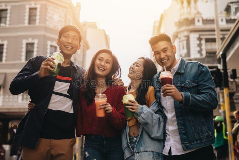Unga vänner på stadsgatan med fruktsaft arkivbilder