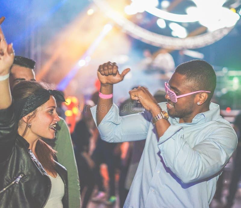 Unga vänner som dansar på fest i nattklubb - Diverse kulturer som njuter av helgens nattliv med originallaserljus royaltyfri bild