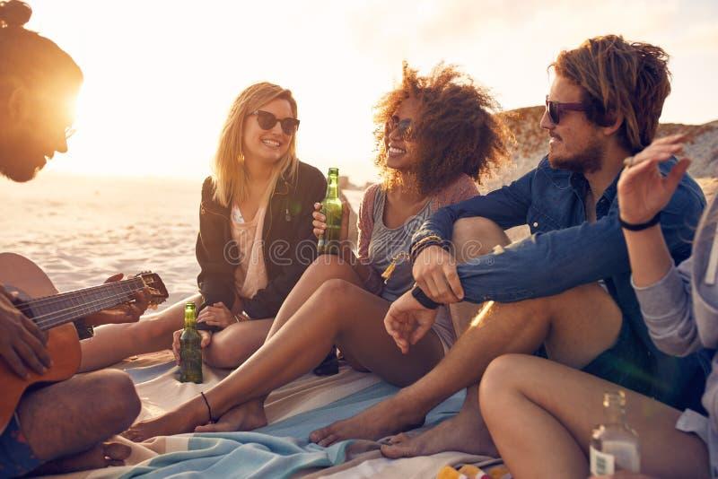 Unga vänner som festar på stranden royaltyfria foton