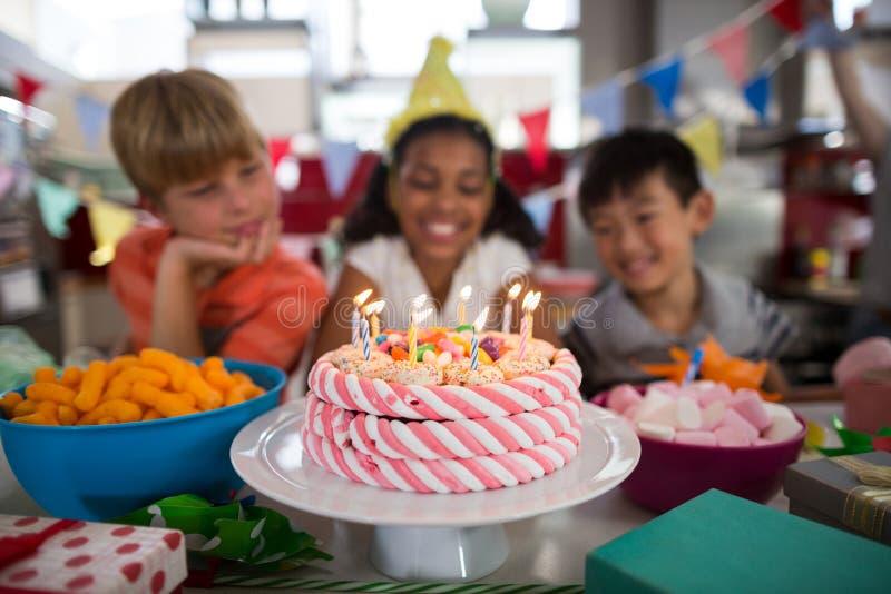 Unga vänner som firar födelsedag i kök royaltyfri bild