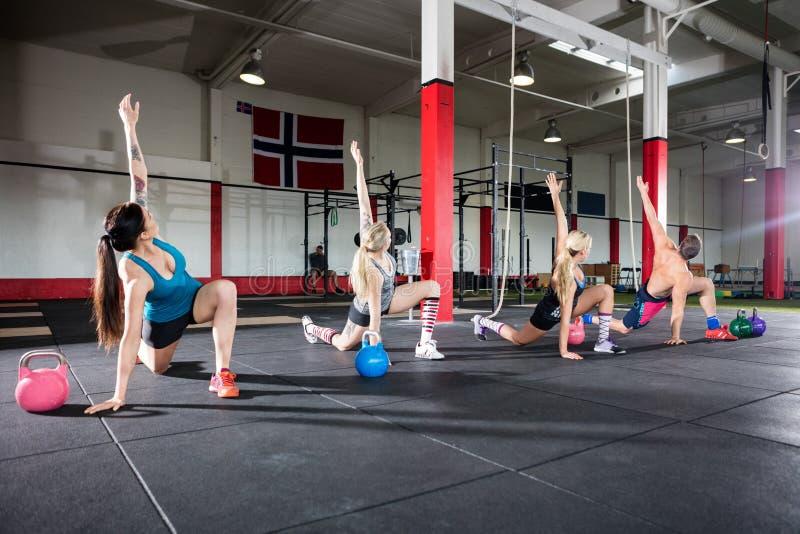Unga vänner som gör sträcka övning i idrottshall royaltyfria foton