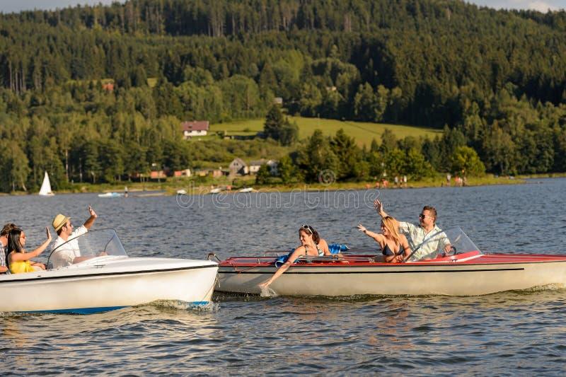 Unga vänner som har gyckel i motorboats royaltyfria bilder