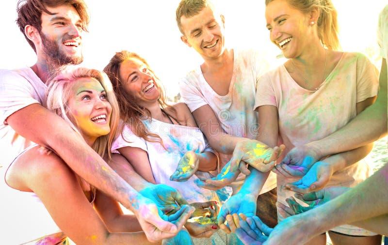 Unga vänner som har gyckel på strandpartiet på holifärgfestival - lyckligt folk som spelar samman med äktt bekymmerslöst lynne royaltyfri foto